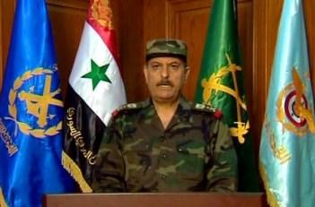 Le nouveau ministre syrien de la défense, le Général Fahd Jassem Al-Freij. Sa nomination consacre un durcissement de la position de Damas. En arrière plan de gauche à droite, le drapeau de la marine, le drapeau national syrien, le drapeau de l'armée de terre et celui des forces aériennes.