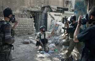 Image prise par le photographe du journal Le Monde montrant des hommes armés en Syrie arborant des masques à gaz.