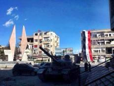Un vieux char de l'armée syrienne au centre-ville d'Al-Nabak (Qalamoun) que l'armée syrienne vient de reprendre après de durs combats avec les factions rebelles. En arrière-plan, les militaires ont déployé un grand drapeau syrien le long d'une façade.