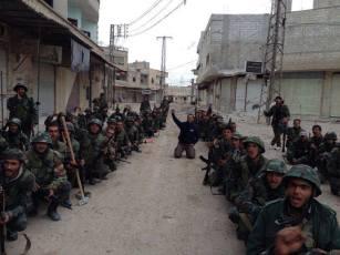 Troupes syriennes durant un moment de repos. Au milieu, le journaliste syrien Hassan Murtaza.
