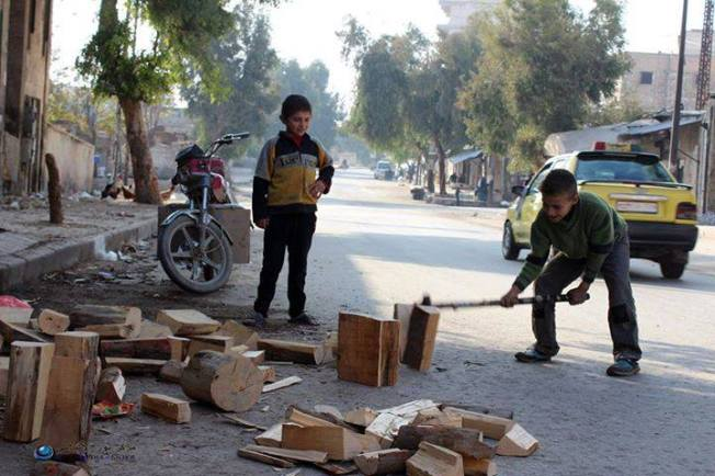 Enfants syriens coupant du bois pour se réchauffer. Alep, mars 2015. Jadis capitale industrielle du pays, Alep a subi de plein fouet les destructions de la guerre. Les services de bases n'y sont plus assurés et le niveau de vie des populations a atteint un seuil très bas.