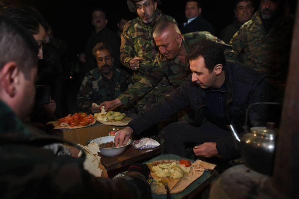 Le président syrien Bashar Al-Assad partageant un repas avec des militaires dans un poste avancé à Jobar, fief rebelle, près de Damas, l'un des lieux les plus dangereux de Syrie. Photographie prise le 01 janvier 2015.
