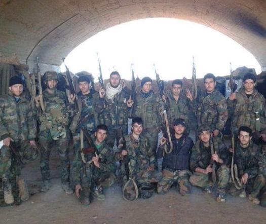 Photographie de groupe de soldats syriens armés d'AKM dans un hangar pour avion de la base aérienne assiégée de Kwaires prise en 2014. Notez que quasiment l'ensemble de ces militaires syriens n'a bénéficié d'une permission depuis novembre 2012.