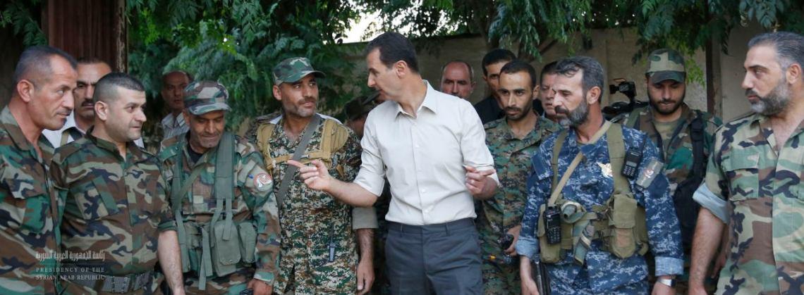 Le président de la République Arabe Syrienne au milieu de soldats, usés par un terrible conflit sans fin, relevant des différentes armes des forces armées syriennes